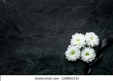 Funeral symbols. White flower near black ribbon on black background top view space for text