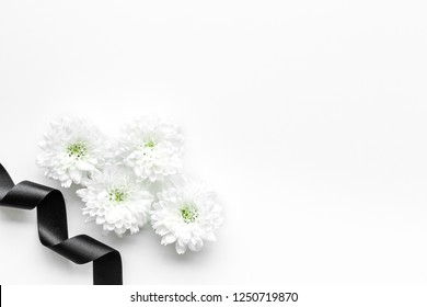 Funeral symbols. White flower near black ribbon on white background top view copy space