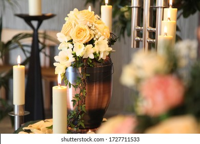 A funeral urn stands with lit candles in a cemetery chapel just before the funeral service.