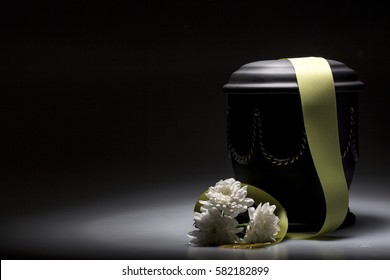 funeral urn, with tape and flower decorated, for sympathy, card