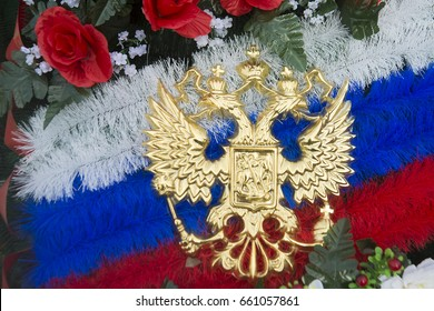 Funeral wreath, colors of the Russian flag, two-headed eagle. Wreath of artificial roses and carnations in russian tricolor and emblem of Russian coat of arms in form of double-headed eagle