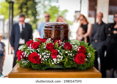 Funerary urn with ashes of dead and flowers at funeral. Burial urn decorated with flowers and people mourning in background at memorial service, sad and grieving last farewell to deceased person.