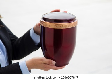 Funerary urn held by two hands on white background
