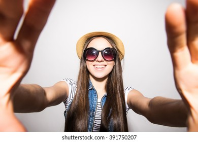 Funky beauty with mobile phone. Portrait of beautiful young woman in glasses and funky hat holding mobile phone