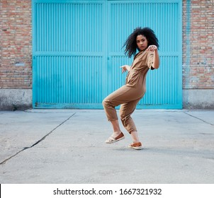 funky black woman dancing alone in the street.  Attractive African woman dancing smiling at the camera.