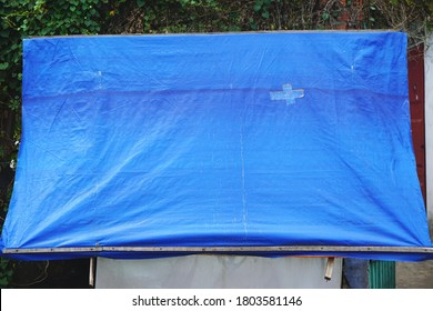Funky blue plastic tarp with crisscross bandage patch