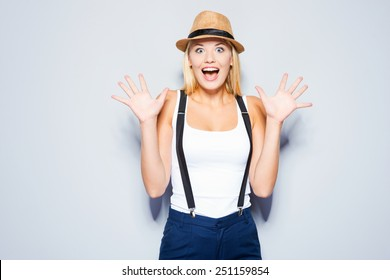 Funky emotions. Beautiful young blond hair women making a face while standing against grey background