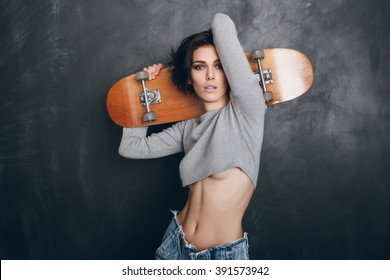 Funky girl posing with skateboard. Lifestyle portrait