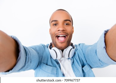 Funky swag selfie! Young african teen hipster is taking selfie shot on pure white backgound, amazed, extremely happy, wearing casual smart