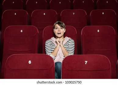 Funky woman watching a movie alone at the cinema