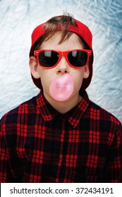 Funky young boy wearing red sunglasses, red baseball cap and a red checked shirt is blowing pink bubbles with his bubble gum.