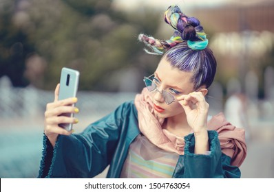 Funky young girl with crazy fashion style hair taking selfie on street – Woman with avant-garde look