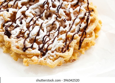 Funnel cake topped with powdered sugar and chocolate drizzle close up, selective focus