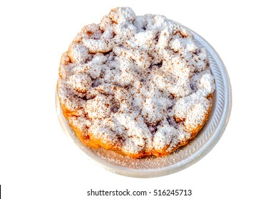 A funnel cake topped with powdered sugar isolated on a white background. Funnel cake is a regional dish popular in the United States at carnivals, fairs, sporting events, and seaside resorts