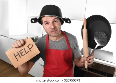 funny 30s Caucasian man holding pan and household with pot on his head in red apron at home kitchen asking for help unable to cook showing panic on cooking with funny face expression