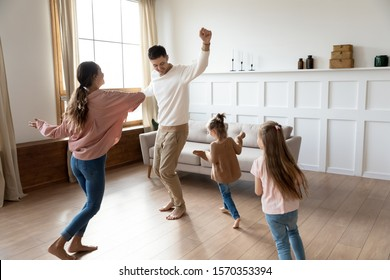 Funny active family of four young adult parents and cute small children daughters dancing together in living room interior, carefree little kids with mum dad having fun laughing enjoy leisure at home - Shutterstock ID 1570353394