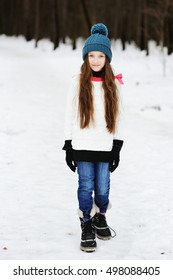 Funny adorable little girl in grey warm coat and hat having fun in beautiful winter park