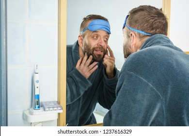 Funny adult man wearing eyemask on forhead having troubles with waking up. Standing in front of mirror looking at his dark circles under eyes, being tired and sleepy.