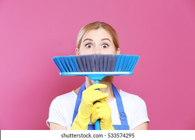 Funny adult woman with floor brush on color background, close up