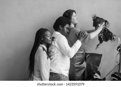 Funny african american couple and caucasian girl with chicken in her hands standing all together on  wall background in studio. Odd people concept
