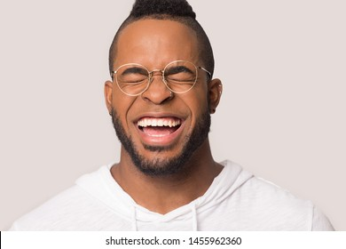 Funny African American man with wide healthy smile laughing at joke close up, happy male in glasses having fun, enjoy laughter, positive emotion, isolated on studio background copy space
