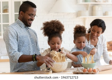 Funny African American parents helping cute kids to knead dough, enjoying kitchen activities. Happy family with children baking dessert for dinner together. Couple teaching son and daughter to cook