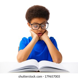 Funny African American school boy reading book with surprise. Teenager with eyeglasses, shocked. Isolated, over white background, with copy space.