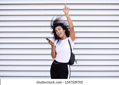 Funny African girl listening to music and dancing with earphones and smartphone outdoors. Arab woman in sport clothes with curly hairstyle in urban background. Female with closed eyes.