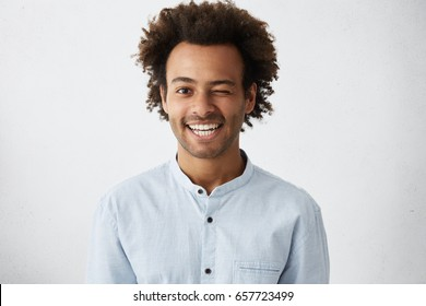 Funny African man with bushy curly hair blinking his eye having warm broad smile wearing white elegant shirt posing in studio. Mixed race man elegantly dressed having fun and good mood making grimace