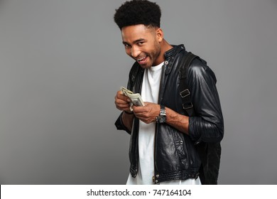Funny african man with stylish haircut greedily considers money, looking at camera, isolated over gray background