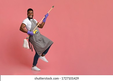 Funny African Man Using Mop Handle As Guitar, Having Fun During Cleaning. Posing Over Pink Background In Studio, Copy Space