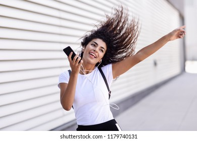 Funny African woman listening to music and dancing with earphones and smartphone outdoors. Arab girl in sport clothes with moving curly hairstyle in urban background.