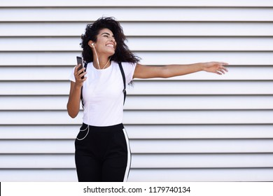 Funny African woman listening to music and dancing with earphones and smartphone outdoors. Arab girl in sport clothes with curly hairstyle in urban background.