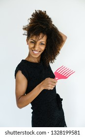 Funny afro hairstyle woman using comb for untangle her curly hair. Black female beauty and style tips concept.