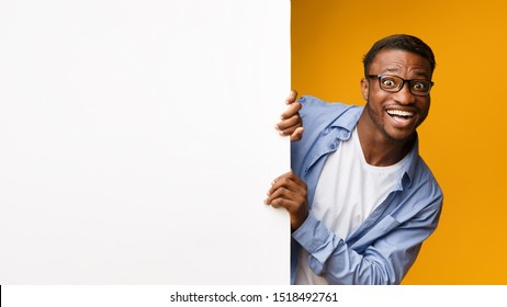 Funny Afro Man Looking Out Of White Blank Board For Text Standing Over Yellow Studio Background. Panorama, Mockup