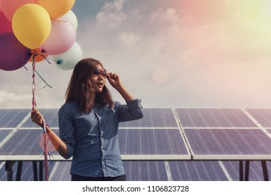 funny Aian girl holding colorful balloon with a Solar panel, photovoltaic in the  summer, Concept of Eco-friendly ,clean energy , Pure energy and Sustainable energy