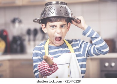 Funny angry boy chef shouting in the kitchen