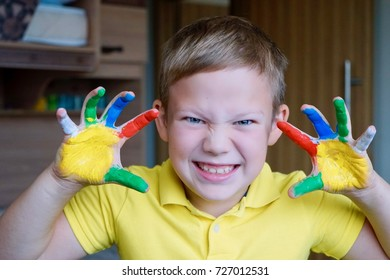 Funny angry boy with painted hands in a yellow t-shirt