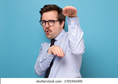Funny angry handsome young man in blue shirt standing in karate gesture and ready to attack. Indoor studio shot, isolated on blue background