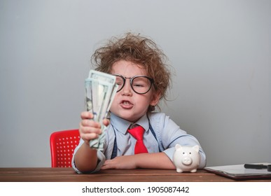 Funny angry kid boss with money. Portrait of angry displeased little child with freckles isolated over white background wearing glasses and suit. Child clenches money in a fist