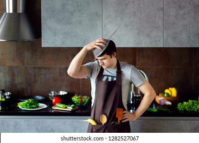 Funny angry loser man male guy with metal sieve on head, frying pan and wooden kitchen utensils trying to cook, failed and yell on grey modern loft kitchen. Unsuccessful bachelor on kitchen concept.