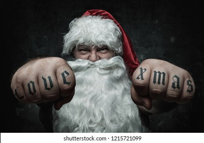 Funny angry Santa Claus showing fists with tattoo
