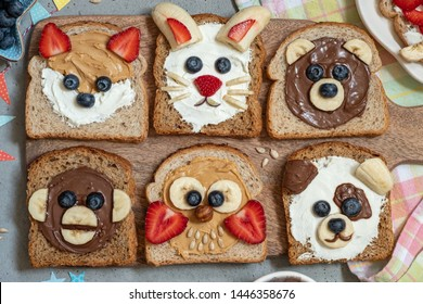 Funny animal faces toasts with spreads, banana, strawberry and blueberry