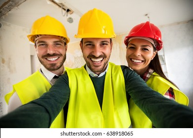 Funny architects workers taking selfie at contruction site, teamwork