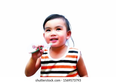 Funny asian baby girl brushing her teeth, healthy concept dental hygiene, isolated on white background.