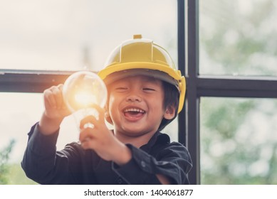Funny Asian boys hold a light bulb that shines in their hands.Sustainable alternative concept work,Child with future of alternative energy and sustainable energy,Eco-Friendly and Pure energy Concept