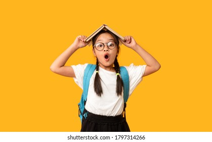 Funny Asian Elementary School Girl Posing With Book On Head Standing Over Yellow Background. Studio Shot