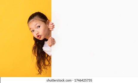 Funny asian girl hiding behind blank white advertising billboard with copy space and peeking out, yellow studio wall