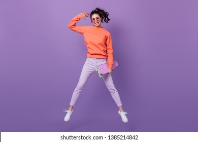 Funny asian girl in pants jumping on purple background. Full length view of korean young woman with longboard.