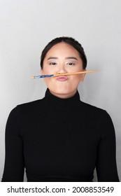 una chica asiática divertida juega con palos de comer orientales mientras te mira, vestida de negro con un fondo aislado e iluminado